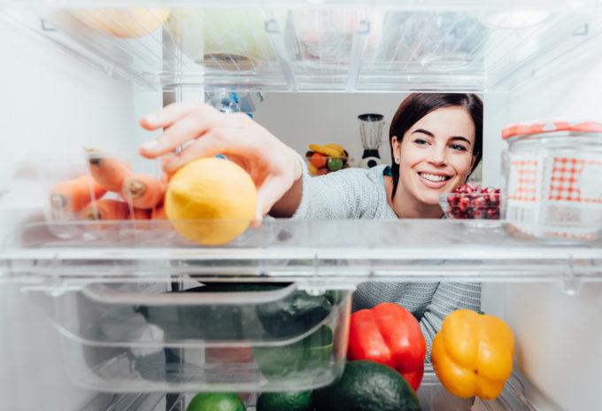 Woman taking lemon out of the fridge